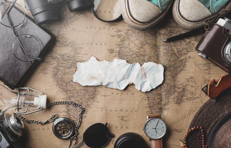 被烧的纸旅行概念背景拷贝空间  旅客的辅助部件顶上的看法在老葡萄酒地图的 免版税库存图片