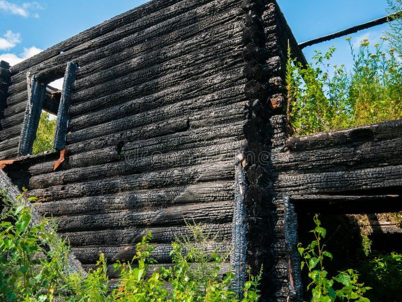 被烧的被破坏的房子门面外部,在灰的黑木墙壁在火以后 免版税库存照片