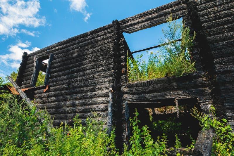 被烧的被破坏的房子门面外部,在灰的黑木墙壁在火以后 库存照片