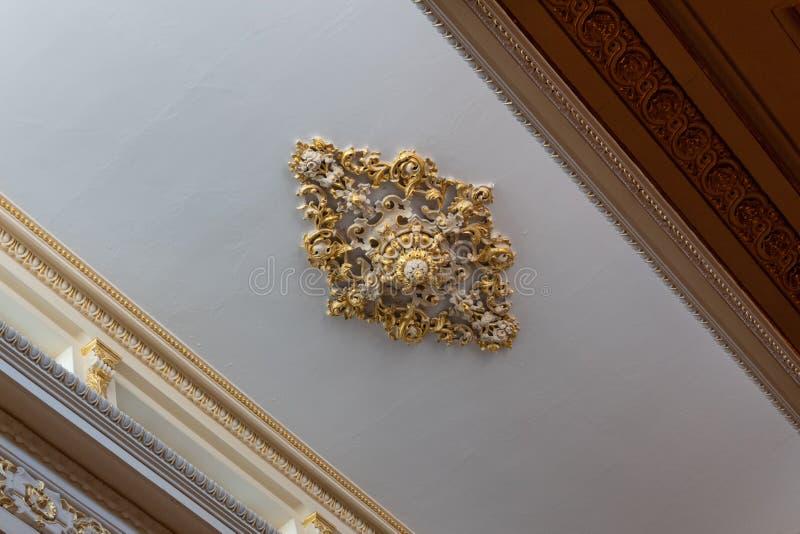 被熔铸的膏药精心制作的天花板大奖章和金叶、美丽的檐口和带状装饰工作 免版税库存照片