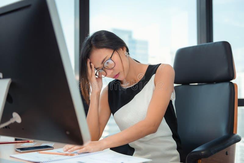 被用尽疲乏和头疼的女实业家画象,当工作在她的办公室时 事务Financail和医疗保健 免版税库存照片