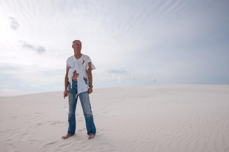 被用尽的人,失去在沙漠,在沙丘站立 免版税库存图片