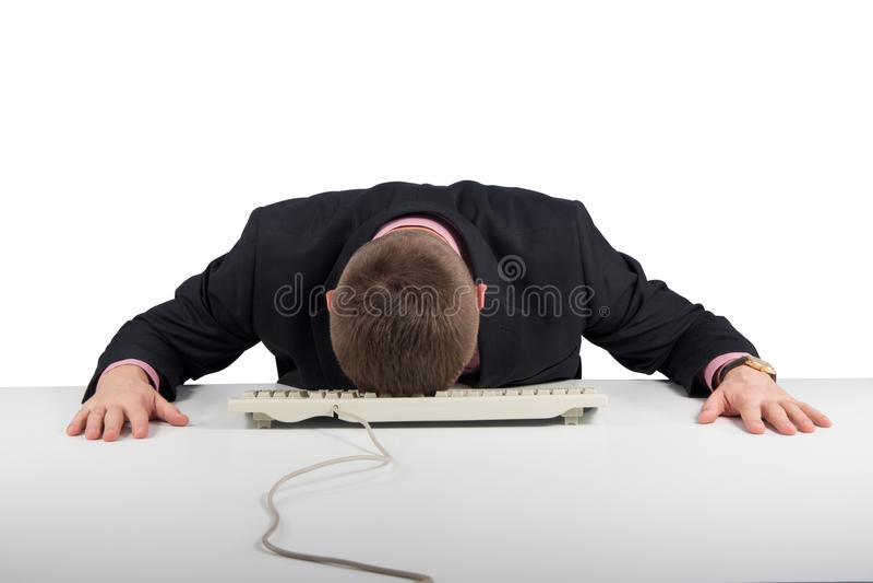 被用尽的商人睡着在白色隔绝的他的办公桌 免版税库存图片