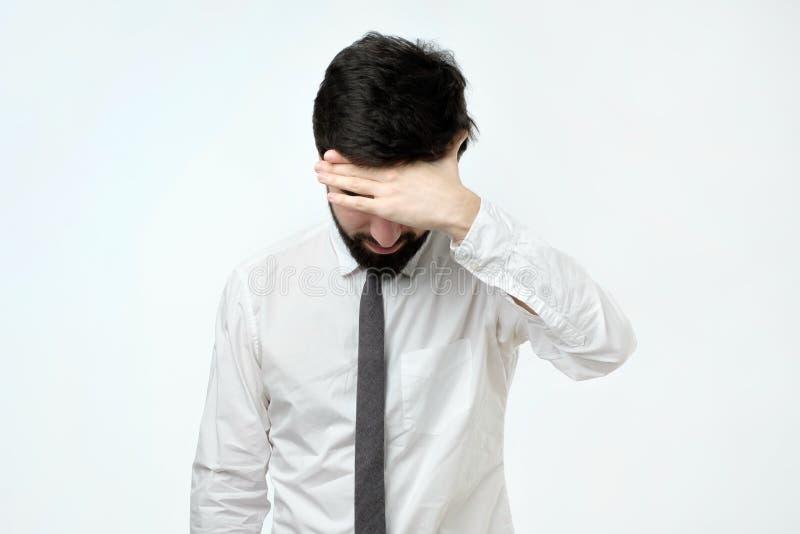 被用尽的年轻人覆盖物面孔用手,当站立反对灰色背景时 图库摄影