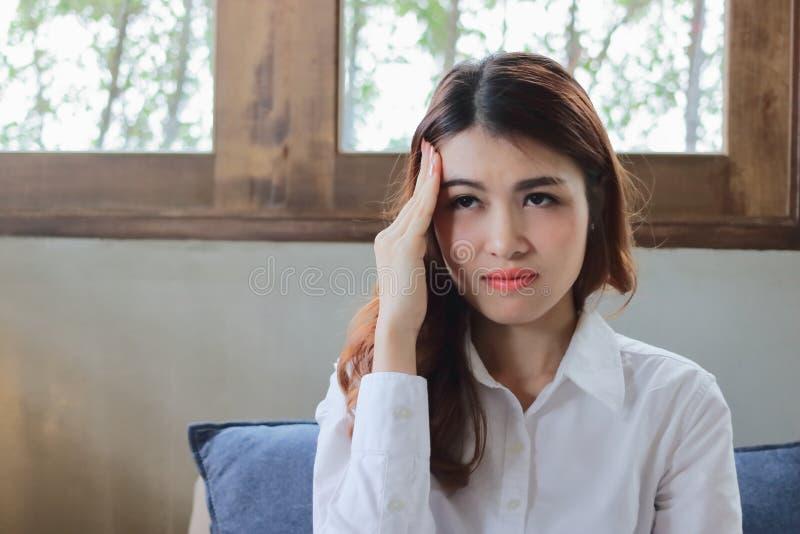 被用尽的沮丧的年轻亚裔女实业家用在感到的前额的与他的工作的手疲乏和烧坏 挫败注重了 免版税图库摄影