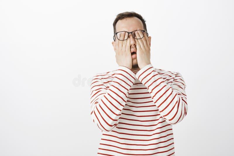 被用尽的难受的男性模型画象在镶边套头衫的和玻璃、摩擦的眼睛,感觉的痛苦或者是 库存图片