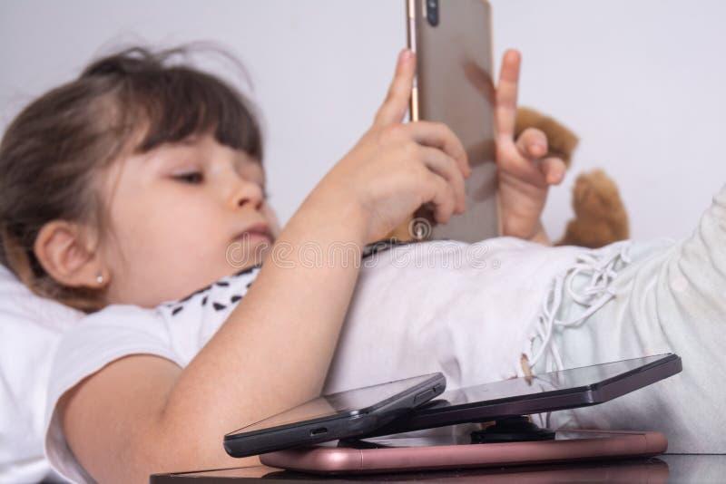 被电话流动应用程序占据心思的女孩在家忽略父母和玩具,使用智能手机检查人脉onl的孩子 库存图片