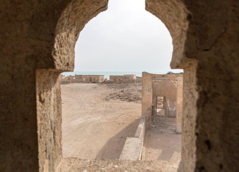 被破坏的古老阿拉伯圈纹窄花边,渔镇Al Jumail,卡塔尔 波斯湾海岸的沙漠  在尖塔窗口外面的看法 库存图片