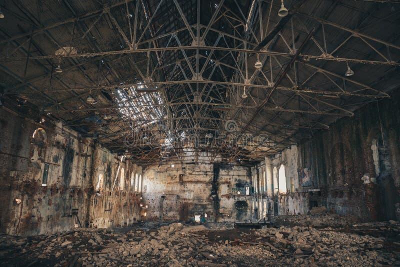 被破坏的和被放弃的黑暗的蠕动的工厂房屋建设里面,工业仓库大厅等待的爆破 免版税库存图片