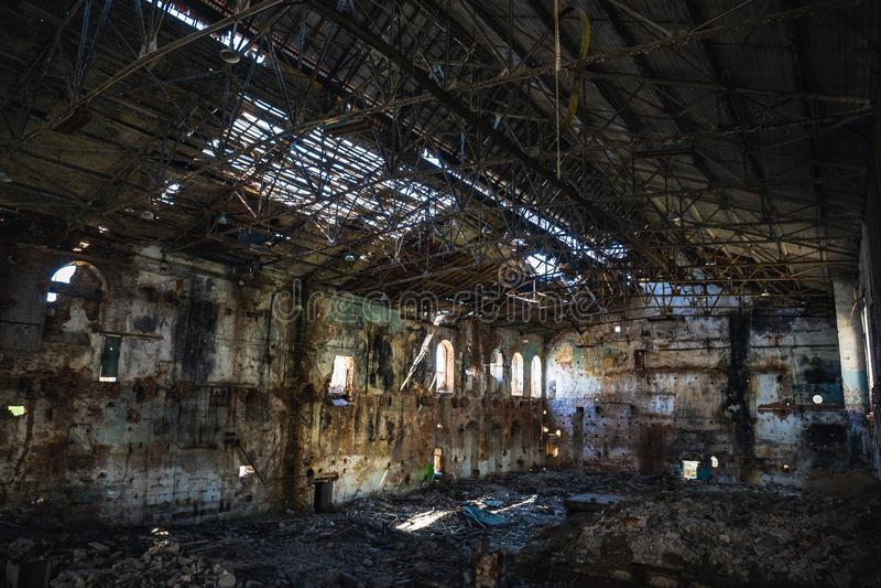 被破坏的和被放弃的黑暗的蠕动的工厂房屋建设里面,工业仓库大厅等待的爆破 图库摄影