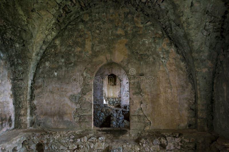 被破坏的大厅内部有破裂,损坏的墙壁和走廊的在圣Hilarion古老城堡,凯里尼亚 库存照片