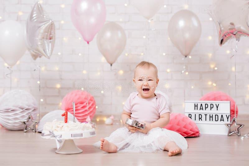 被碰撞的党概念-哭泣的女婴和捣毁的蛋糕在砖墙有光和气球的 免版税库存图片