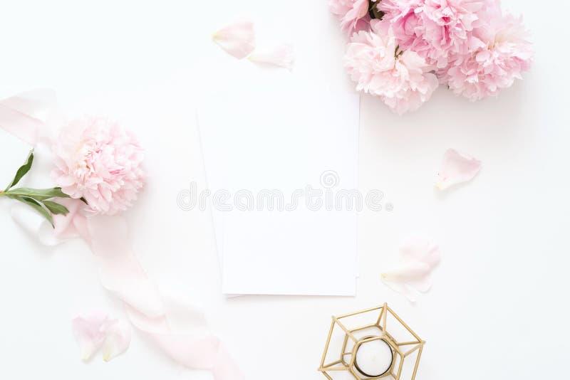 被称呼的女性顶视图 在与喜帖的白色背景,桃红色牡丹瓣,蜡烛 免版税库存照片
