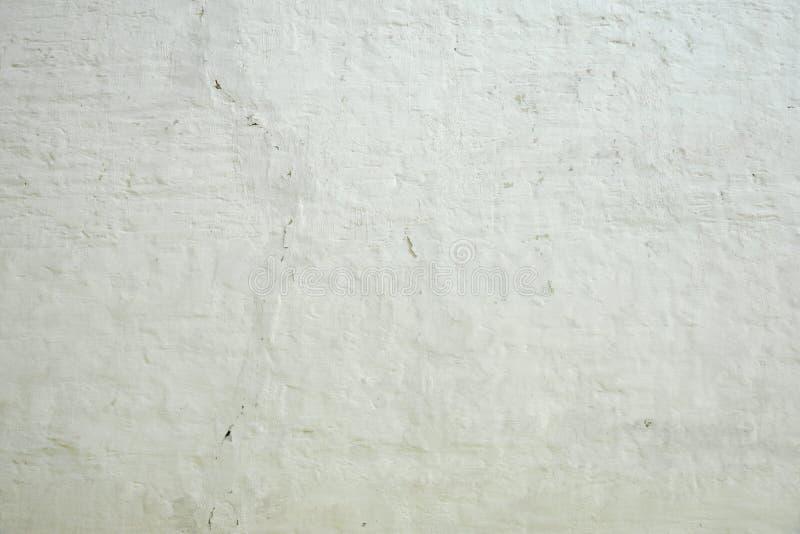 被粉刷的老砖墙参差不齐的七高八低的概略的土气背景 库存照片
