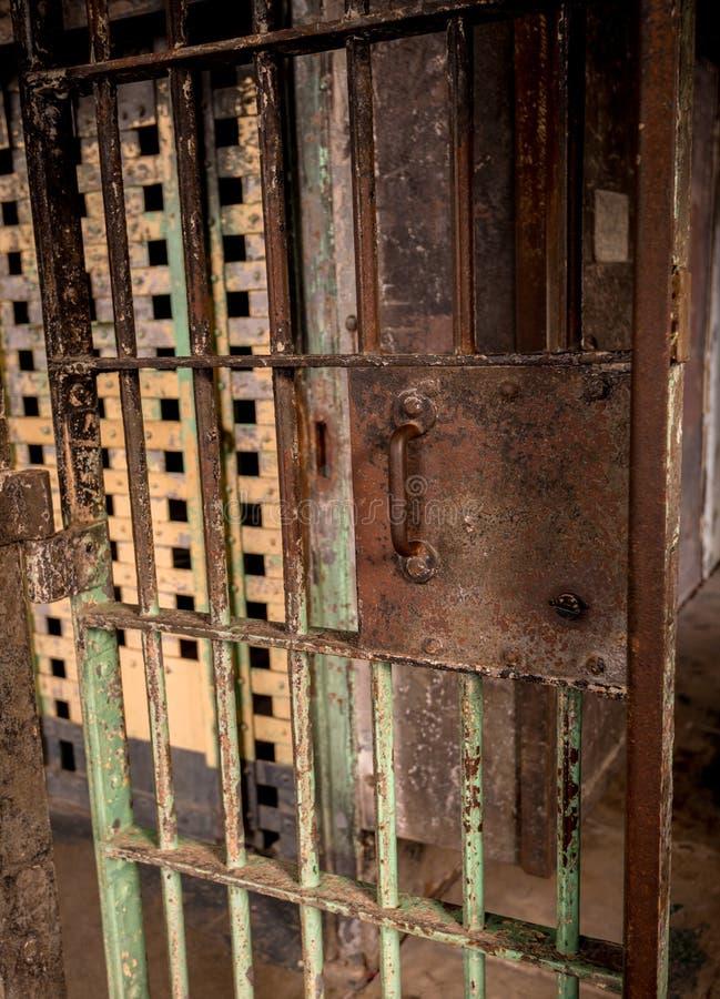 被绘的和生锈的老监狱门导致走廊 图库摄影
