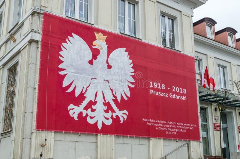 被绘的徽章波兰的 与金黄额嘴和爪的被加冠的老鹰,在红色背景 免版税图库摄影