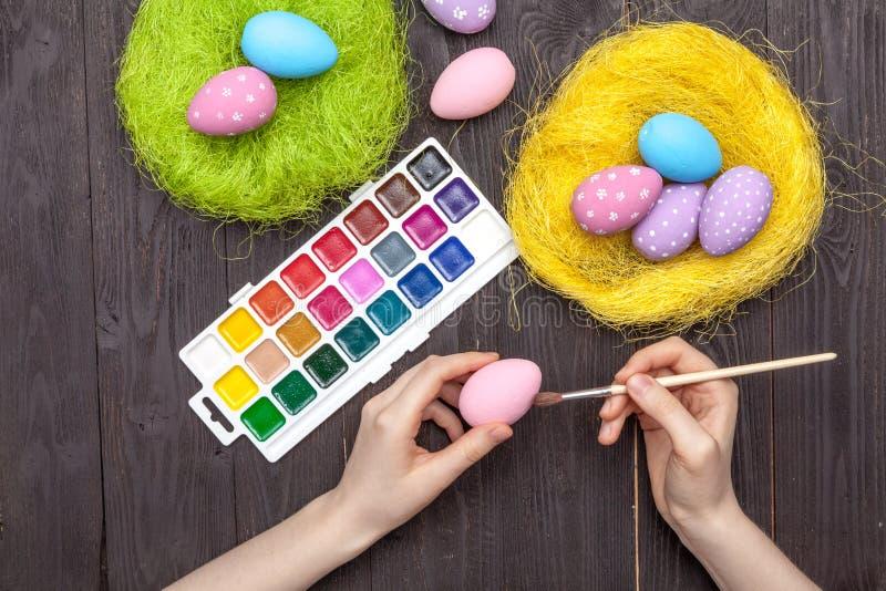 被绘的装饰复活节彩蛋、刷子、调色板和油漆 库存图片