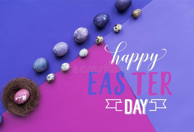 被绘的鸡行和鹌鹑蛋和巢与愉快的复活节天字法在背景 免版税库存图片
