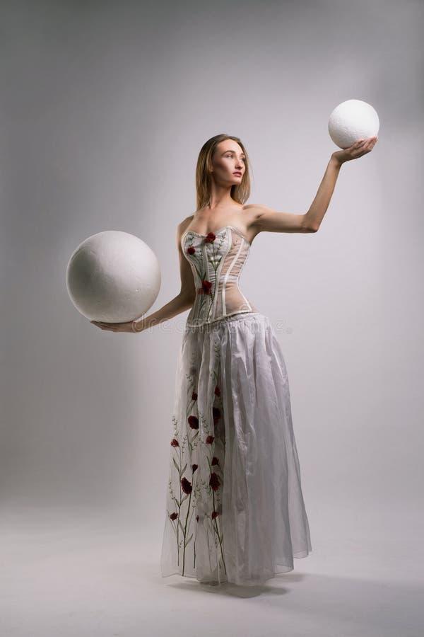 被绣的白色束腰和长的裙子的女孩 库存照片