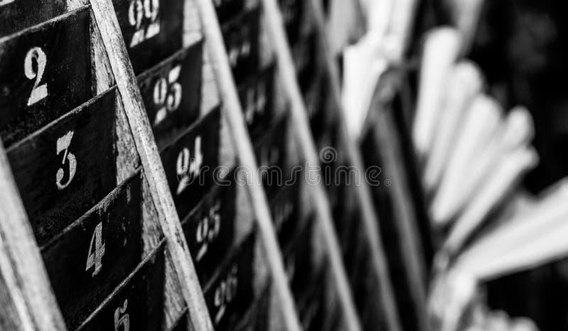 被编号的老和退色的时钟打孔卡墙壁机架 免版税库存照片