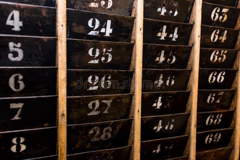 被编号的老和退色的时钟打孔卡墙壁机架 库存照片