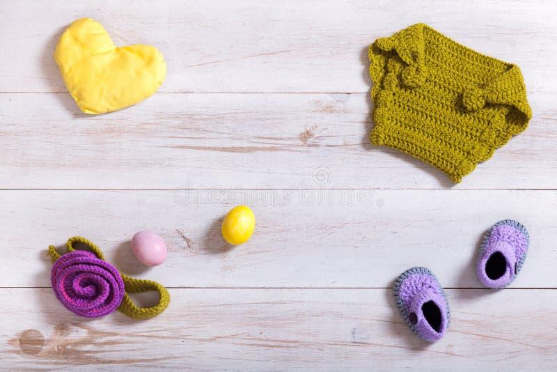 被编织的婴孩衣裳和辅助部件在白色木背景,新出生的手工制造衣物集合,孩子项目在桌上,儿童时尚 免版税库存照片
