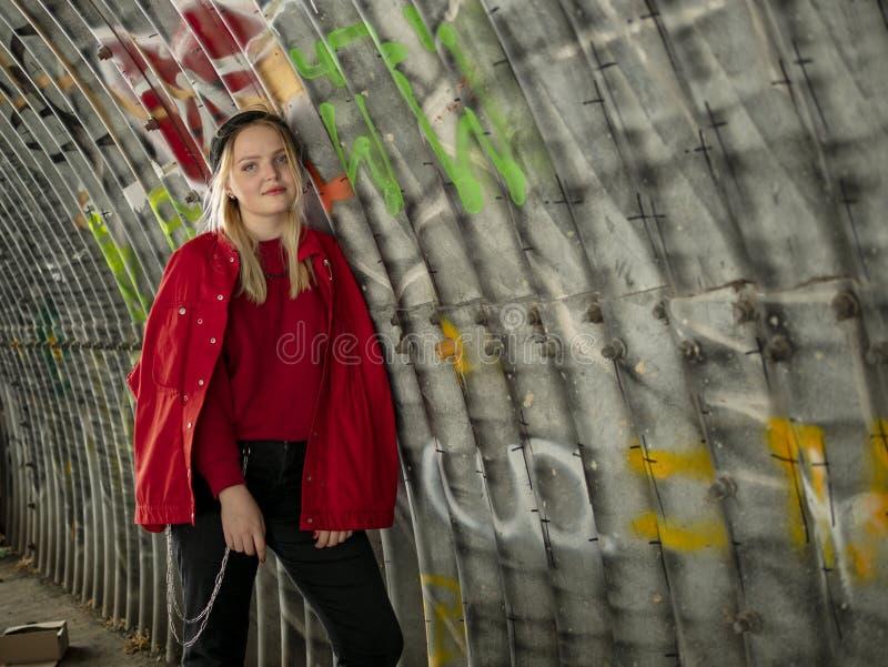 被编织的帽子和红色夹克的可爱的年轻行家女孩站立在桥梁下以墙壁为背景与 库存图片