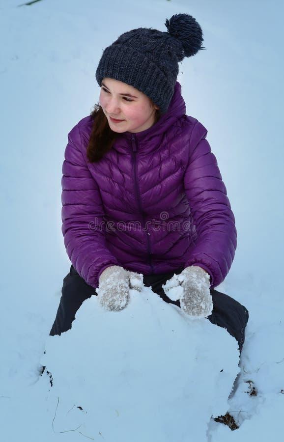 被编织的帽子和黎明夹克的青少年的女孩有巨大的雪球的做雪人 免版税库存图片