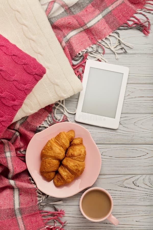 被编织的枕头和格子花呢披肩、eBook、新月形面包和咖啡在lig 免版税库存照片
