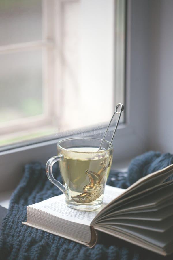 被编织的毛线衣杯子热的在窗口的茶开放书 舒适冬天秋天天 自然光地道平静的大气 ?? 免版税库存图片