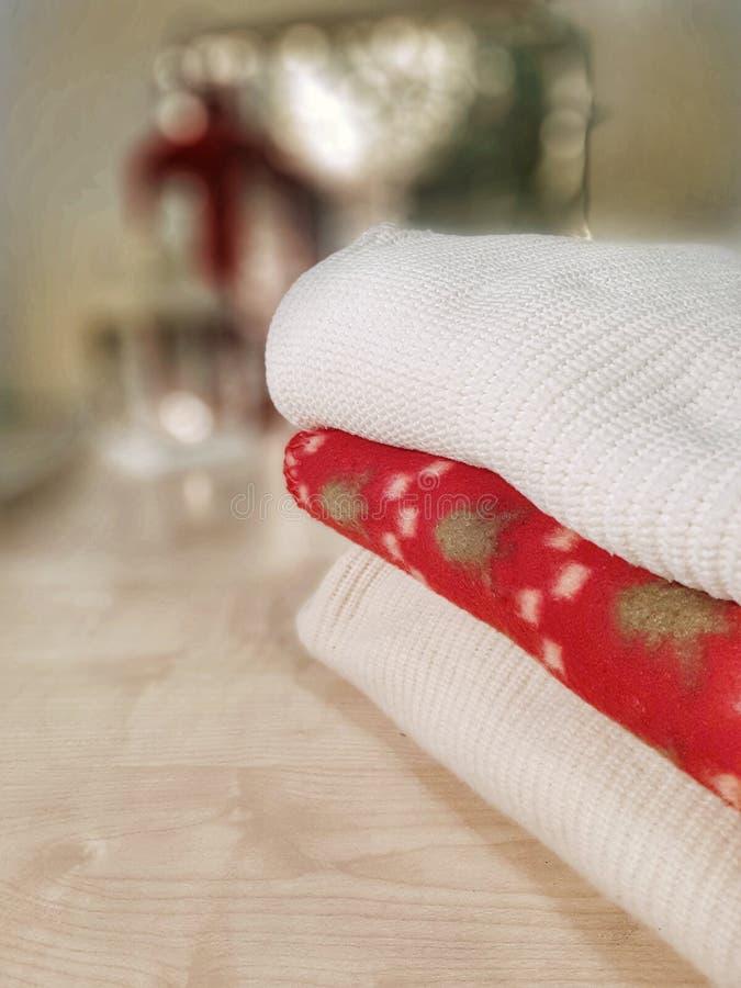 被编织的毛线衣,在木桌上的红色羊毛格子花呢披肩 Bokeh作用 库存照片