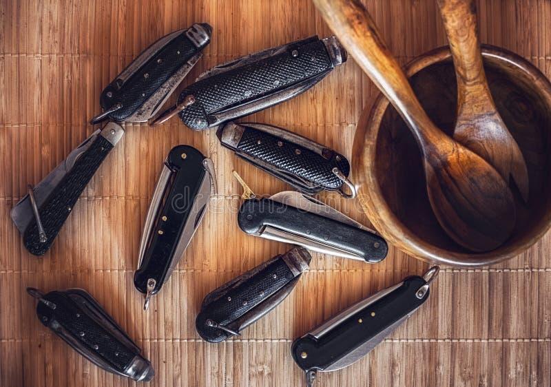 被编织的秸杆枝杈表面上的葡萄酒船舶航行索具刀子与有木利器的碗 免版税库存照片