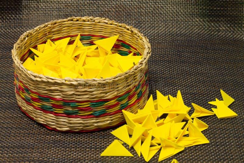 被编织的秸杆篮子与黄色纸的 免版税库存照片