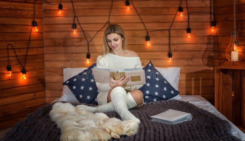 被编织的衣裳的一名妇女坐一张床在乡间别墅里并且读书和饮用的热的茶 库存照片
