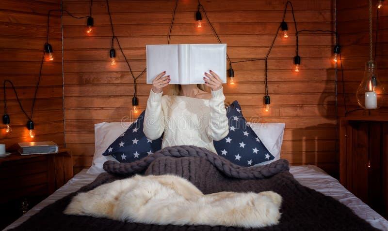 被编织的衣裳的一名妇女坐一张床在乡间别墅里并且读书和饮用的热的茶 免版税库存照片