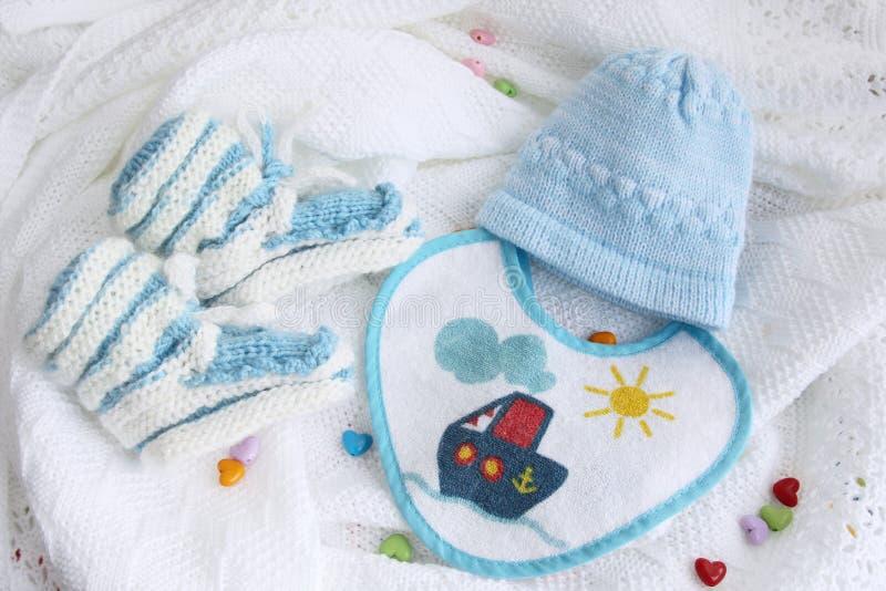 被编织的新出生的婴孩赃物、帽子和围嘴在钩针编织的一揽子白色背景与五颜六色的心脏 免版税库存图片