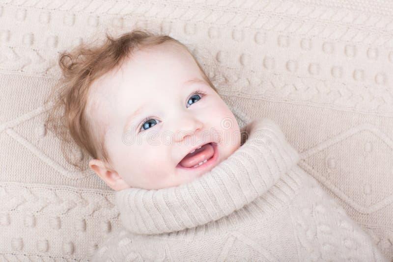 被编织的毛线衣的逗人喜爱的女婴在被编织的毯子 免版税库存图片