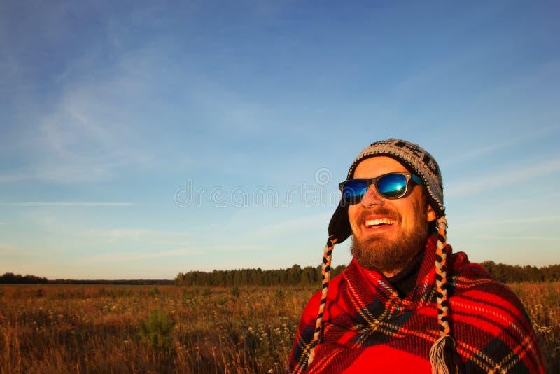 被编织的盖帽、太阳镜和毯子的年轻微笑的人是日出会议在领域和蓝天的背景的 库存图片