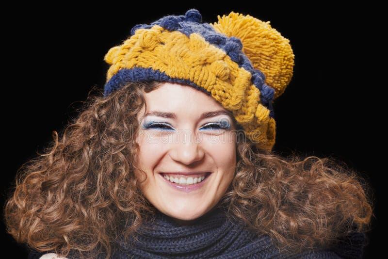 被编织的滑稽的帽子的年轻美丽的妇女 免版税库存照片