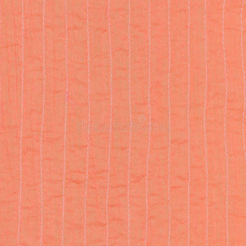 从被缝的丝绸的珊瑚颜色纺织品背景 免版税库存图片