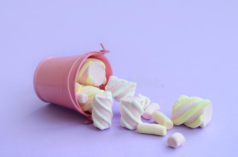 被翻转的微型桃红色桶充满在紫色淡色背景的蛋白软糖谎言 最小的概念 免版税库存照片