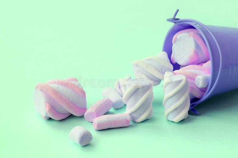 被翻转的微型淡紫色桶充满在绿松石柔和的淡色彩背景的蛋白软糖谎言 库存照片