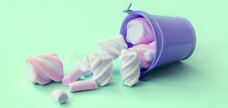 被翻转的微型淡紫色桶充满在绿松石柔和的淡色彩背景的蛋白软糖谎言 免版税库存图片