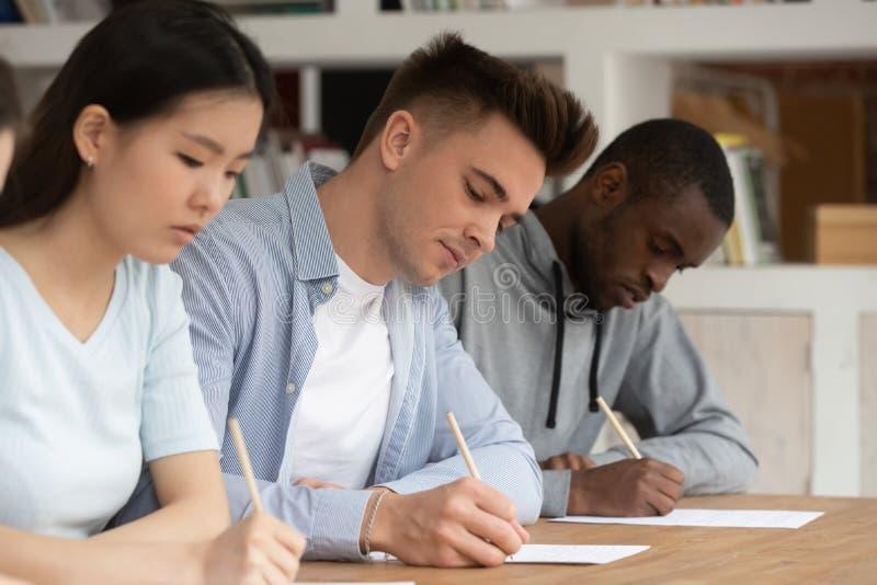 被聚焦的不同种族的年轻人写通过检查在学校 库存图片