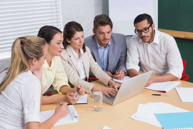 被聚焦的企业队开会议使用膝上型计算机 免版税库存图片