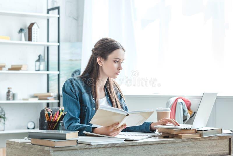 被聚焦的十几岁的女孩藏品书和使用膝上型计算机,当学习时 库存照片
