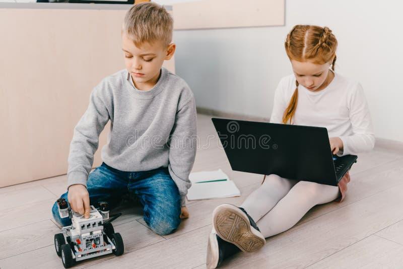 被聚焦的孩子坐地板在词根与机器人的教育类 图库摄影