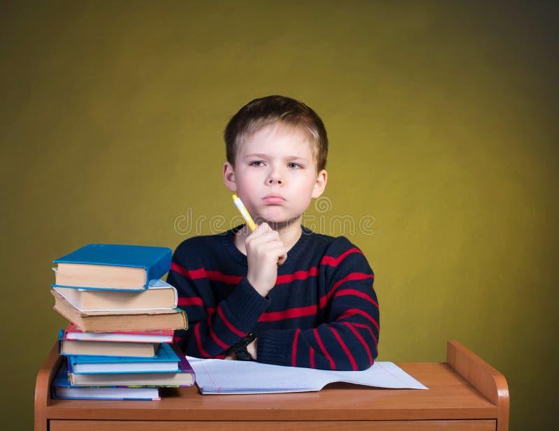 被聚焦的孩子学习 疲乏的小男孩文字 免版税库存照片