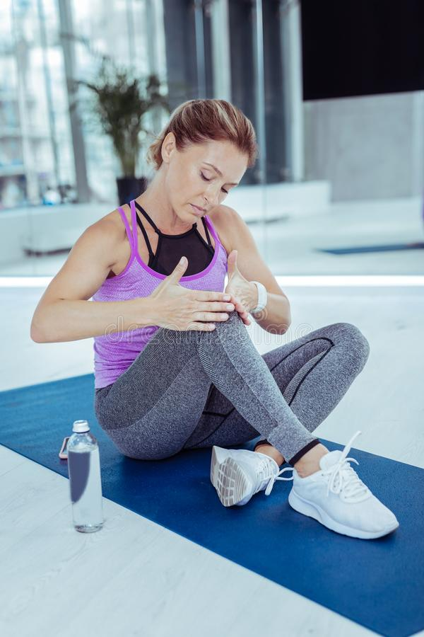 被聚焦的成熟妇女有伤害在锻炼以后 免版税库存照片