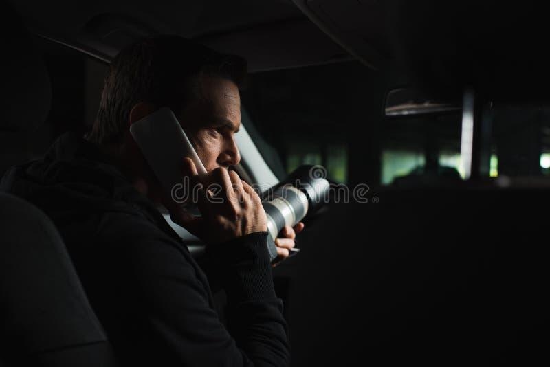 被聚焦的男性无固定职业的摄影师做监视由照相机和谈话在汽车男性的智能手机 库存图片